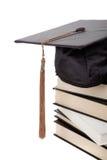Staffelungschutzkappe oben auf einen Stapel Bücher auf Weiß Lizenzfreie Stockbilder