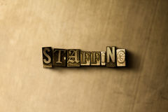 STAFFING - close-up of grungy vintage typeset word on metal backdrop. Royalty free stock - 3D rendered stock image.  Can be used for online banner ads and Stock Image