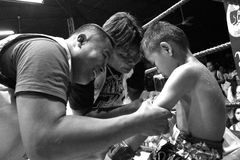 Staffs of boxing team take care of young Thai boxer Stock Image