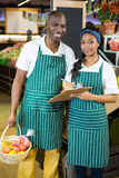 Staffs members maintain records on clipboard in supermarket Stock Image