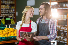 Staffs using digital tablet in organic section. Smiling staffs using digital tablet in organic section of super market Royalty Free Stock Images