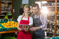 Staffs using digital tablet in organic section. Smiling staffs using digital tablet in organic section of supermarket Royalty Free Stock Images