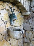 Stag Head Fountain Ornament. Tarnished metal stags head ornament above non functional household stone fountain, in stone enclosure stock photos