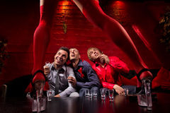 Stag party. Three men sitting in front of dancing women. They are looking confused and shocked. Front view Stock Photos