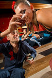 Stag party. Man giving glass of whisky to stripteaser women on stage Royalty Free Stock Photography