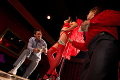 Stag party. View of two men offering money to a stripper on stage Stock Images