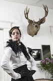 Stag's head. A woman in Edwardian style dress posing in the room below a stag's head hanging on the wall royalty free stock images