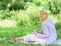 Stag som är fritt med avlägset jobb Klara av avlägsen det fria för affär Kvinnan med bärbara datorn sitter gräsängen Bästa jobb a arkivbild