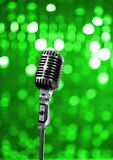 On stage. Retro microphone on green background Royalty Free Stock Images