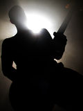 On stage. A guitarist on stage, silhouetted by bright lights Royalty Free Stock Image