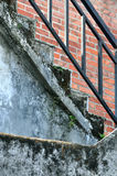 Stage on aged building. Stair with handrail on aged architecture with moss, shown as composition in part detail of architecture and a kind of people living Royalty Free Stock Photography