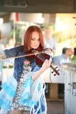 On stage - beautiful, frail and slender girl with fiery red hair - a well-known musician, virtuoso violinist Maria Bessonova. Enchanting expressive show lady Royalty Free Stock Photos