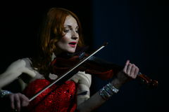 On stage - beautiful, frail and slender girl with fiery red hair - a well-known musician, virtuoso violinist Maria Bessonova. Stock Photo