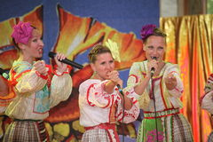 On the stage beautiful girls in national Russian costumes, gowns sundresses with vibrant embroidery - folk-music group the Wheel. Stock Photos