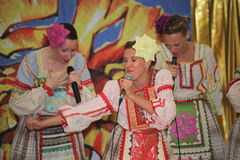 On the stage beautiful girls in national Russian costumes, gowns sundresses with vibrant embroidery - folk-music group the Wheel. Royalty Free Stock Photos