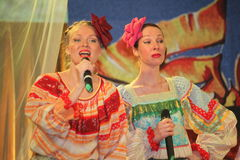On the stage beautiful girls in national Russian costumes, gowns sundresses with vibrant embroidery - folk-music group the Wheel. Stock Images