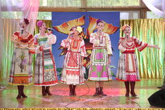 On the stage beautiful girls in national Russian costumes, gowns sundresses with vibrant embroidery - folk-music group the Wheel. Royalty Free Stock Photo