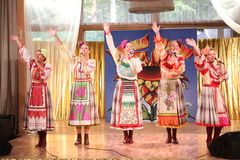 On the stage beautiful girls in national Russian costumes, gowns sundresses with vibrant embroidery - folk-music group the Wheel. Royalty Free Stock Image