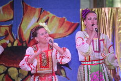 On the stage beautiful girls in national Russian costumes, gowns sundresses with vibrant embroidery - folk-music group the Wheel. Stock Photo