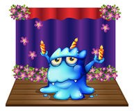 A stage with a blue monster balancing the three lighted candles Royalty Free Stock Photography