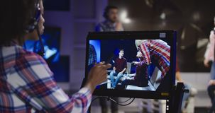 Stage director watching show in record. Casual African-American woman in headset controlling process of shooting TV show standing in front of computer screen and stock footage