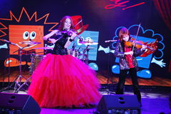 On stage, the expressive red-haired violinist Maria Bessonova sons twins. violin trio two generations of red fiery musicians. Royalty Free Stock Image