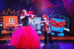 On stage, the expressive red-haired violinist Maria Bessonova sons twins. violin trio two generations of red fiery musicians. Stock Image