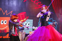 On stage, the expressive red-haired violinist Maria Bessonova sons twins. violin trio two generations of red fiery musicians. Royalty Free Stock Photos
