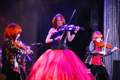 On stage, the expressive red-haired violinist Maria Bessonova sons twins. violin trio two generations of red fiery musicians. Royalty Free Stock Images