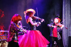 On stage, the expressive red-haired violinist Maria Bessonova sons twins. violin trio two generations of red fiery musicians. Stock Photos