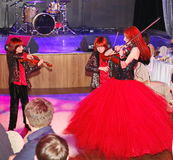 On stage, the expressive red-haired violinist Maria Bessonova sons twins. violin trio two generations of red fiery musicians. Stock Images