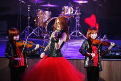 On stage, the expressive red-haired violinist Maria Bessonova sons twins. violin trio two generations of red fiery musicians. Stock Photography