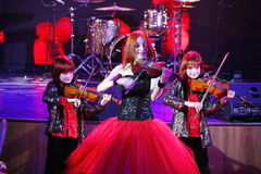 On stage, the expressive red-haired violinist Maria Bessonova sons twins. violin trio two generations of red fiery musicians. Stock Photo