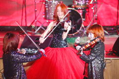 On stage, the expressive red-haired violinist Maria Bessonova sons twins. violin trio two generations of red fiery musicians. Royalty Free Stock Photo