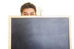 Stage Fright. Man hiding behind a blackboard Stock Photography