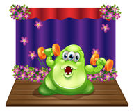 A stage with a green monster exercising in the center Stock Photography