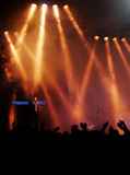 Stage, hands, and lights. Crowd raising hands at a pop concert; lights look like fire; blue keyboard on left side Stock Photography