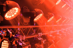 Stage lighting equipment. Red concert spotlight. The direct rays of light in the haze stock photography