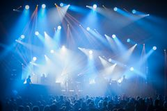 Stage lights on concert. Lighting equipment. With multi-colored beams. Silhouettes of people and musicians in big concert stage Stock Photography