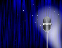 Stage lights microphone blue curtain. Blue curtain background with a microphone. In anticipation of the start Royalty Free Stock Images