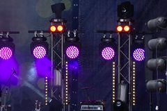 Stage lights. Several projectors in the dark. Purple spotlight strike through the darkness stock photography