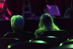 Stage Lights and Spectators. Women in the audience at a concert are illuminated by stage lights royalty free stock images