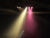Stage lights. Yellow and pink spotlight strike through the darkness royalty free stock image