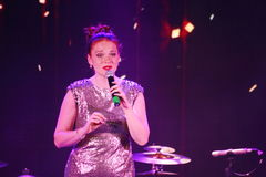 On stage, the musicians pop-rock group Spearmint and singer Anna Malysheva. Red headed Glam Rock Girl singing. Stock Photo