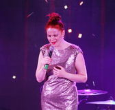 On stage, the musicians pop-rock group Spearmint and singer Anna Malysheva. Red headed Glam Rock Girl singing. Stock Photos