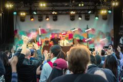 Stage at the pop concert, the viewer`s hand, raised up, blurred stock image