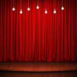 Stage with red curtain, wooden flooring and light bulbs Stock Photography
