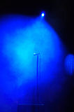 Stage smoke microphone. Single microphone on a stage covered blue tinted light and smoke during a rock concert Stock Images