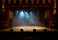 The stage of the theater illuminated by spotlights and smoke. From the auditorium Royalty Free Stock Image