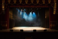 The stage of the theater illuminated by spotlights and smoke. From the auditorium Stock Photo